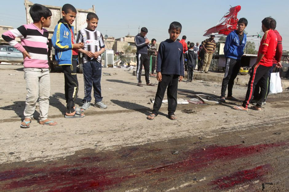 Iraqi Children look at aftermath of a spring bombing in Sadr City, Baghdad (AFP)